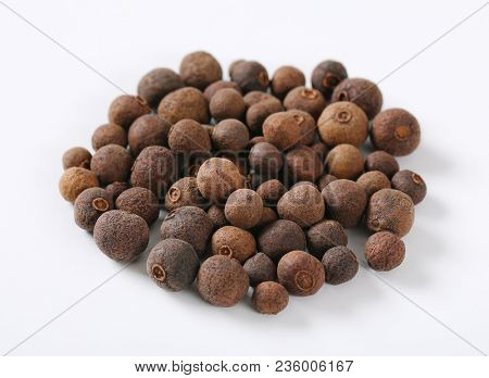 pile of whole allspice berries on white background