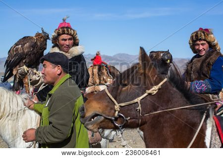 OLGIY, MONGOLIA - SEP 30, 2017: Golden Eagle Hunters at traditional clothing, with a golden eagle on his arm during annual national competition with birds of prey Berkutchi of West Mongolia.