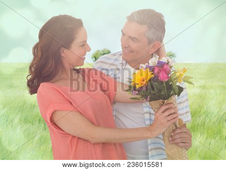 Middle aged couple with flowers in blurry meadow