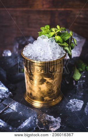 A Small Iron Bucket Stands On A Table With Ice. The Ice In The Tin Can Is Decorated With Mint. Crush