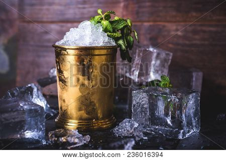A Container With Ice Stands Among Ice Cubes And Mint. A Small Iron Bucket Stands On A Table With Ice