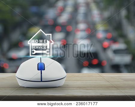 Hammer And Wrench And House Icon With Wireless Computer Mouse On Wooden Over Blur Of Rush Hour With