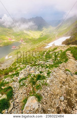 Balea Lake In Fog View From The Top. Lovely Summer Landscape With Low Clouds Around