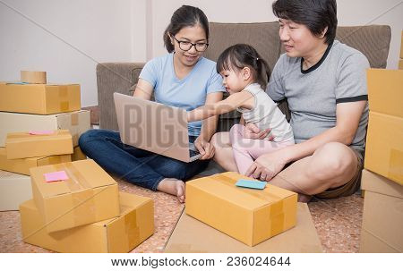 Portrait Of A Little Girl With Her Parents Unpacking Boxes Together
