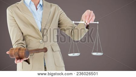 Female judge mid section with scales and gavel against brown background