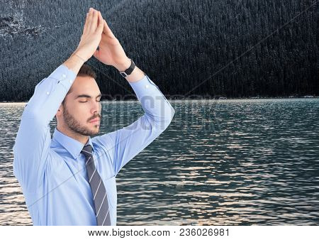 Business man meditating against water and trees on hill