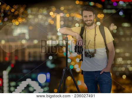 happy photographer rest on tripod in front of the city at night ( with blurred lights) and bokeh ove