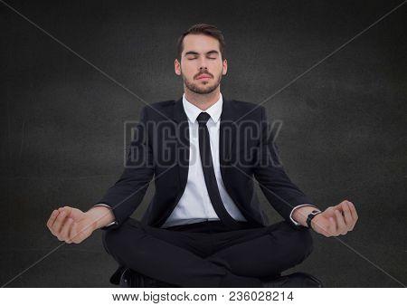 Business man meditating against grey wall