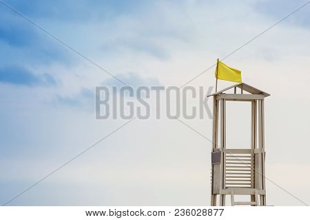 Wooden Watchtower For Lifeguards On The Beach, Against The Sky With Clouds, Concept