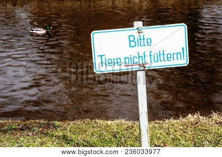 Sign With German Words Please Do Not Feed Animals By A Lake With Duck