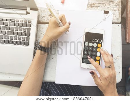 Top View Two Hands Of Women, Right Hand With Calculator On Mobile Phone And Left Hand Writing On Whi