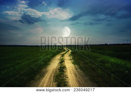 Road Stretching Into The Distance Near The Green Field. Magic Blue Night Sky With Moon And Stars.