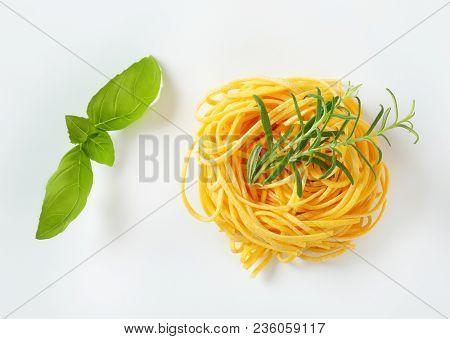 bundle of spaghetti pasta and fresh herbs on white background