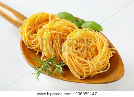 bundles of spaghetti pasta and herbs in wooden scoop - close up