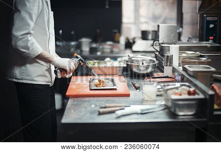 Restaurant Chef Cook Preparing Salmon Filet Flambe. Focus Is On The Salmon, Burner And Cook`s Hand.