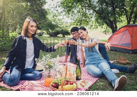 Group Of Friends Enjoying Picnic While Drinking A Orange Juice On Summer Picnic, Leisure, Holidays,