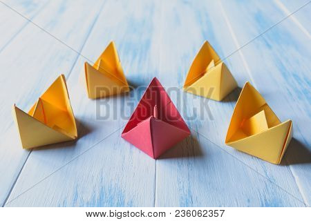 Leadership Concept, Red Leader Boat, Standing Out From The Crowd Of Orange Boats, On Wooden Backgrou
