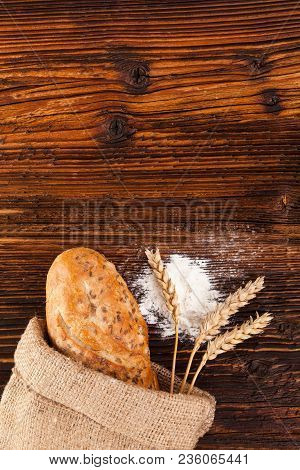 Fresh Homemade Baguette Bread In Burlap Bag With Wheat Ears And Wheat Flour On Wooden Table From Abo