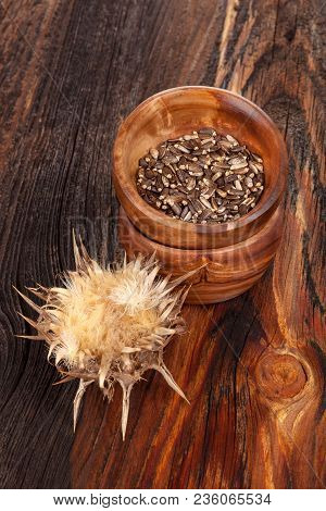 Dried Silybum Marianum, Known As Milk Thistle Flower And Seeds In Wooden Bowl On Wooden Table.