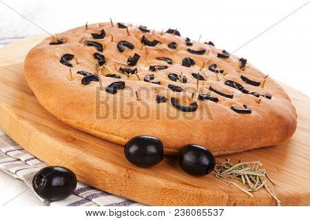 Italian Foccacia Bread With Black Olives On Wooden Choping Board.