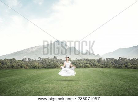 Young Woman Keeping Eyes Closed And Looking Concentrated While Meditating On Cloud In The Air With B