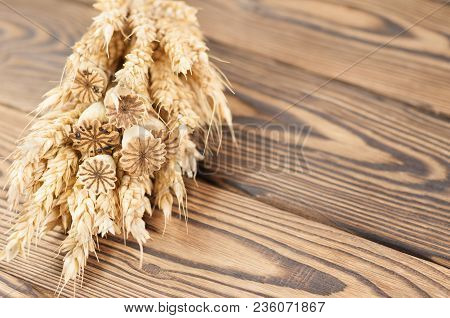 One Bundle Of Wheat And Poppy On Old Rustic Wooden Planks