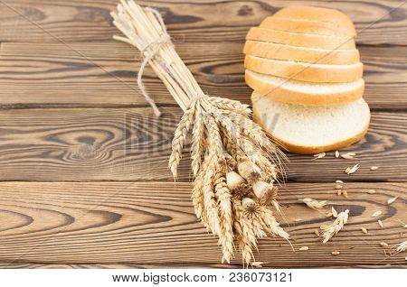 One Bundle Of Wheat And Poppy And Lot Of Scattered Grain And Slices Of Bread On Old Rustic Wooden Pl