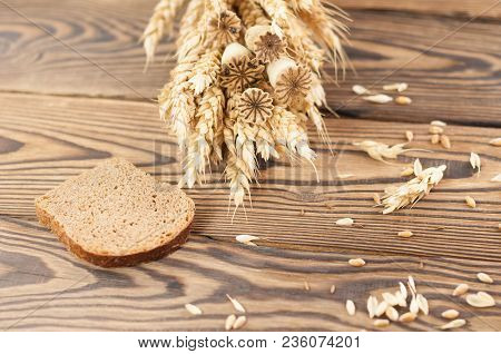 One Bundle Of Wheat And Poppy And Lot Of Scattered Grain And Slice Of Bread On Old Rustic Wooden Pla