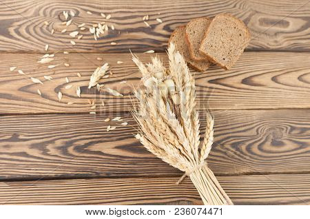 One Bundle Of Wheat And Poppy And Lot Of Scattered Grain And Three Slices Of Bread On Old Rustic Woo