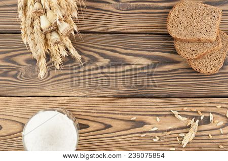 One Bundle Of Wheat And Poppy And Lot Of Scattered Grain And Three Slices Of Bread And Flour In Glas