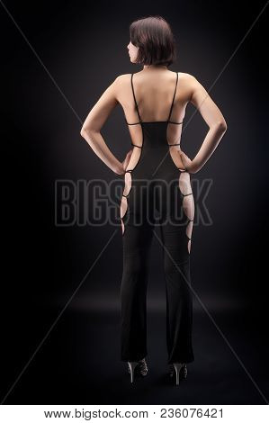Attractive Young Woman With Elegant Overalls At Black Background. Back View