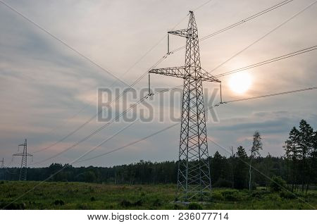 Electricity Pylons With Wires On A Background Of Forest And The Sun Behind The Clouds.