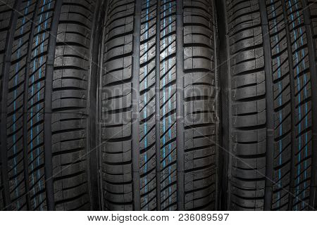 New And Unused Car Tires Against Dark Isolated Background