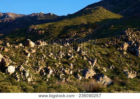 Barren arid landscape including the San Jacinto Mountains with boulders and grasslands taken in Cabazon, CA poster