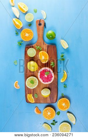 Citrus Food Pattern On Blue Background - Assorted Citrus Fruits With Mint Leaves On Wooden Cutting B
