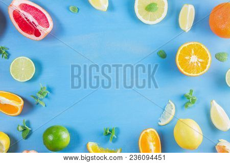 Citrus Food Flat Lay Frame Pattern On Blue Background - Assorted Citrus Fruits With Mint Leaves