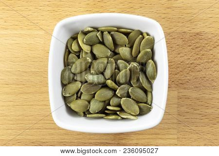 Overhead Shot Of Raw Pepitas, In A White Bowl On A Wooden Chopping Board Background. Pepitas Are She