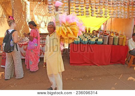 India, Goa, January 24, 2018. Street Trading. Indian Seller Of Street Food In Yellow Clothes. India,