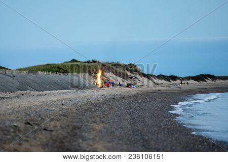 Unidentified people enjoying evening on beach