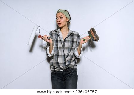 Cute Girl Builder In A Plaid Shirt Doing Repairs In An Apartment, Holding A Brush Hand And A Roller