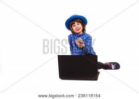 Cheerful Executive Little Boy With Smart Phone And Laptop Sitting Down Isolated On White Background