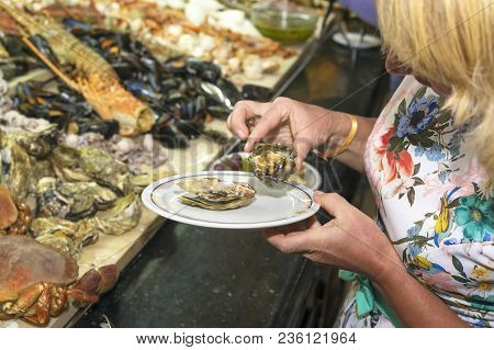The Girl Puts A Plate Of Mussels, Dinner In A Prestigious Restaurant. A Large Selection Of Fresh Sea