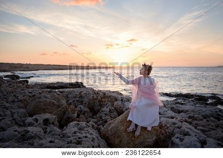 Girl Crowned Princess Meets The Dawn Of The Sun Sitting On A Stone On The Ocean Sea Shore
