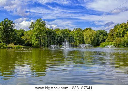 View Of Beautiful City Park With Pond, Fountains, Swimming Ducks, Green Trees And Lawns. Summer Natu