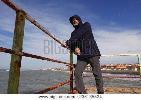 Mature Man And The Sea On A Sunny Windy Day