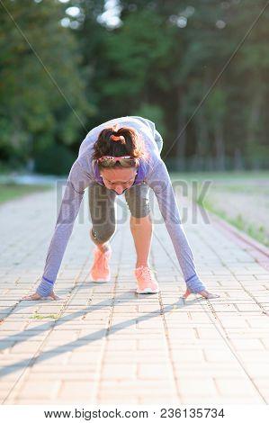 Female Runner Ready For Running Sprint. Girl Is Starting Line Runner Pose For Training In A Park.