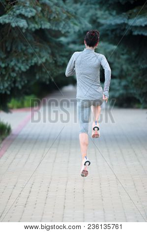 Back View Of Jogging Girl Athlete At Park