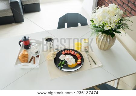 Breakfast With Poached Eggs And Tomatoes, Croissant, Juce And Cup Of Coffee Served On Dinner Table