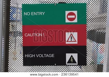 No Entry, Caution And High Voltage Sign With Difference Color Background On Fence