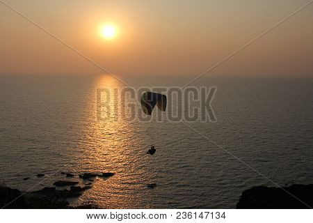 A Paraglider Against The Background Of The Sea And Sunset Or Dawn. Beautiful Seascape. Extreme Sport